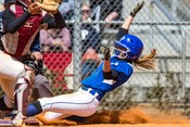 softball player sliding into homebase