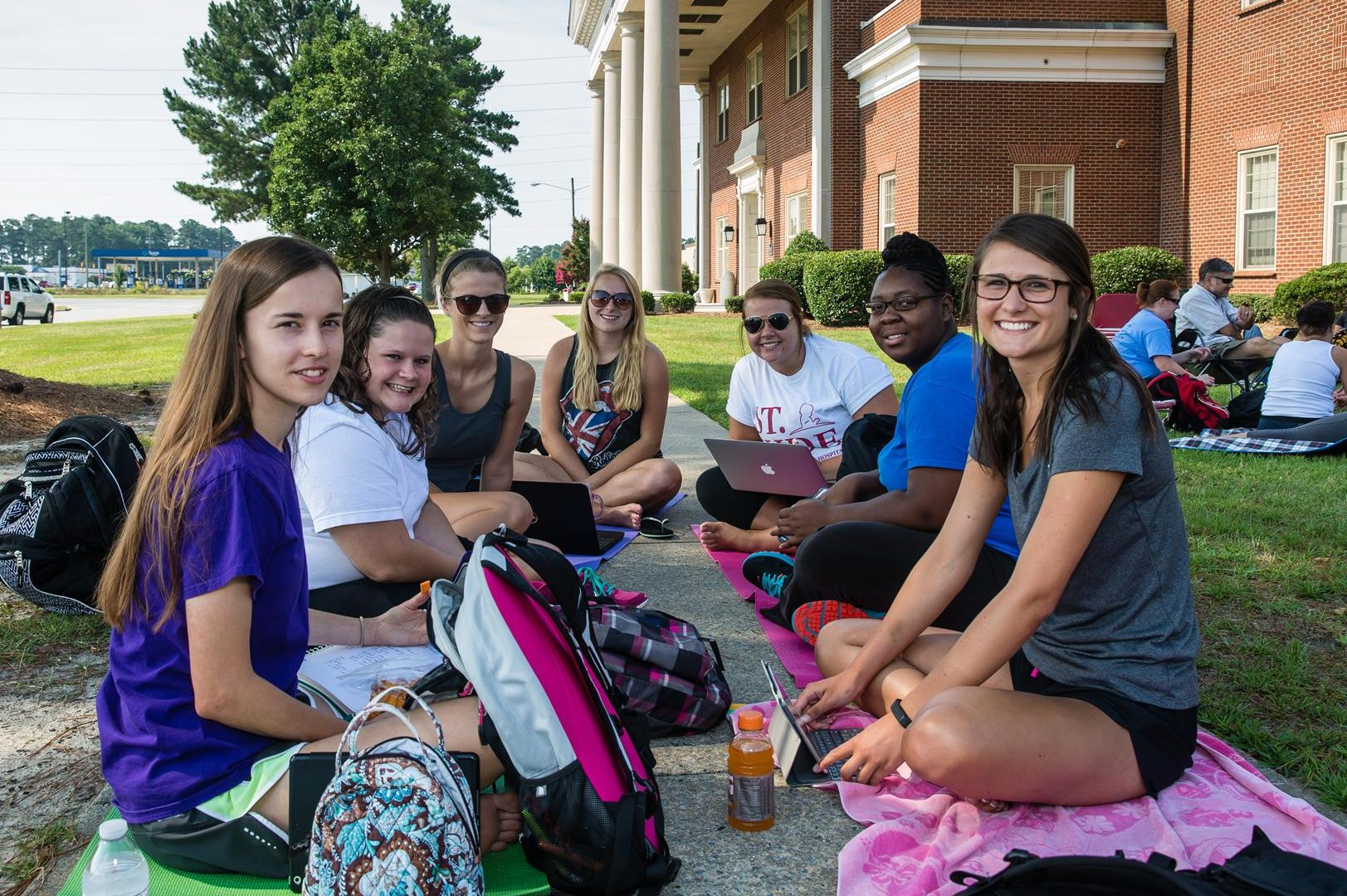 A group of female students sitting on ground outside on campus studying
