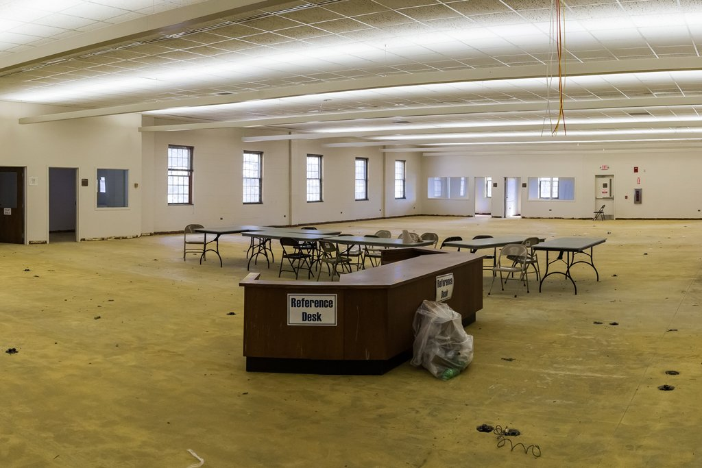Second floor of PCC's library practically empty in preparation for renovations. Only a few tables and the help desk remain.