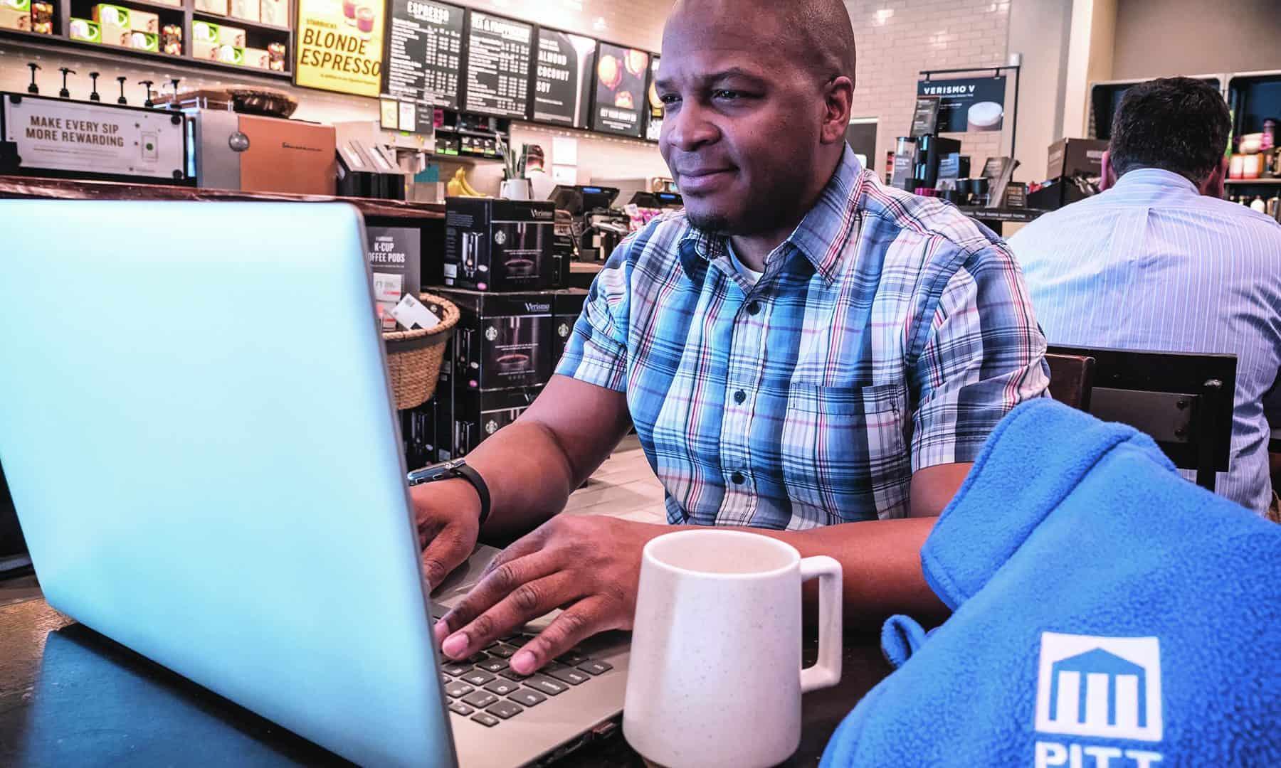 Man woking on computer at cafe