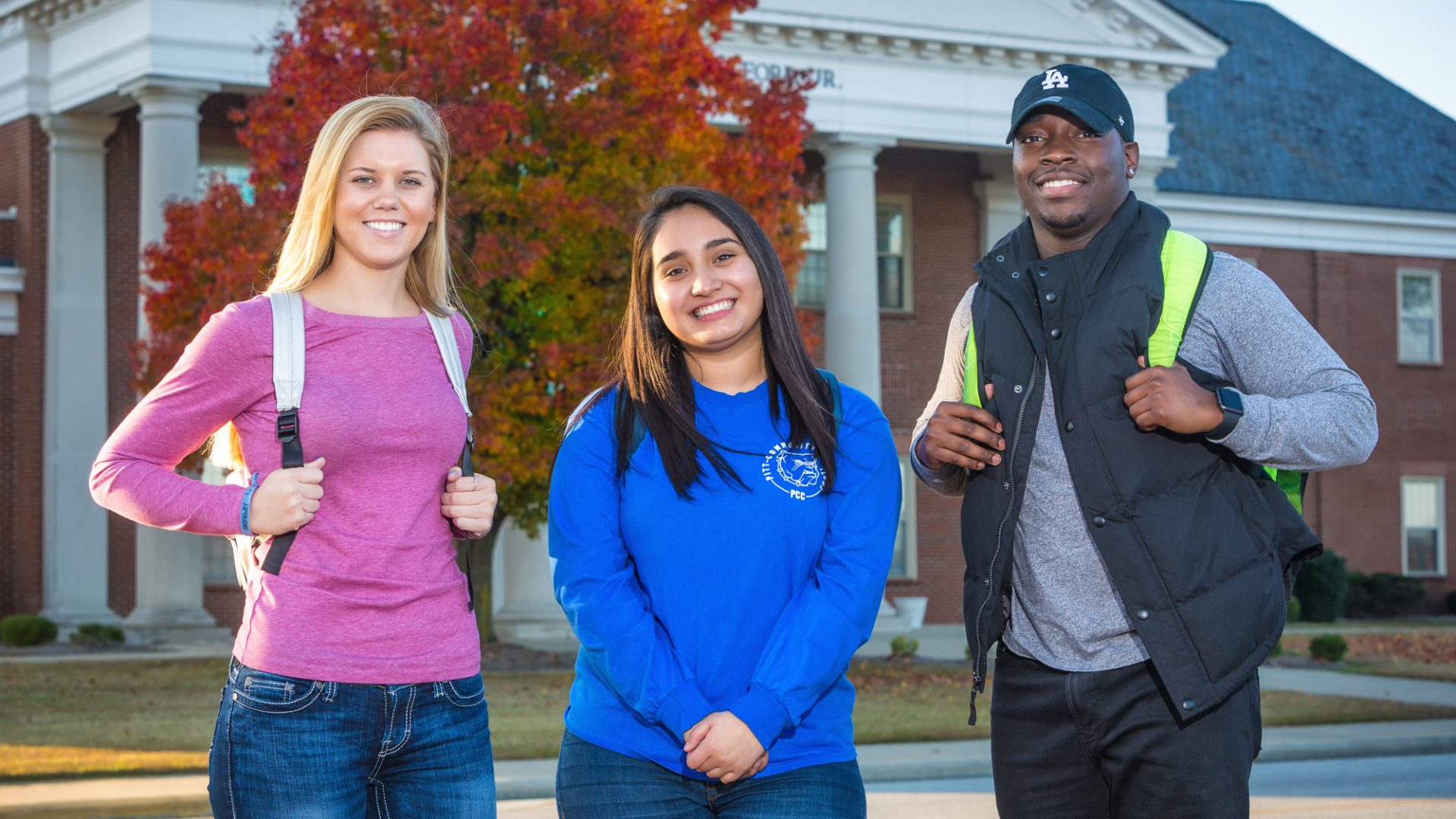 Three students smile as they stand in front of the William Fulford Building during the fall semester.
