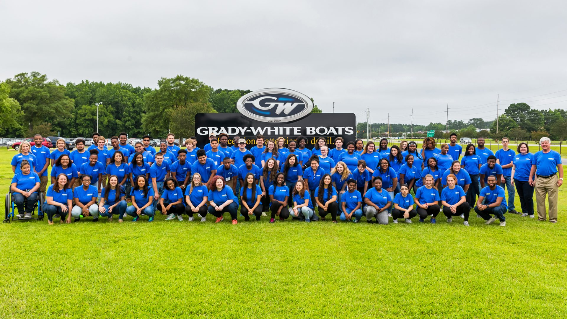 VISIONS staff and students pose for a group photo in front of the Grady-White Boats sign in Greenville.