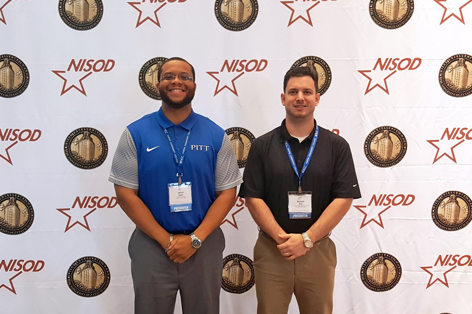 Jasmin Spain and Nicholas Vick pose for a photo in front of a NISOD backdrop.