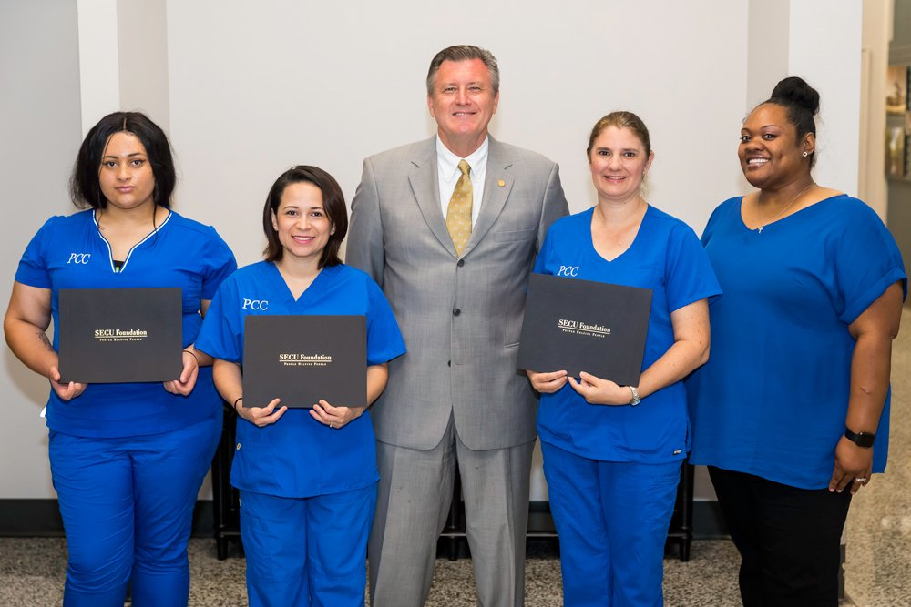 SECU VP/Manager Branch Operations Jeffrey Nelson (center) and PCC Director of Continuing Education Health Care Programs Sidette Brown (right) present SECU Continuing Education Scholarships to PCC students Monique Rascoe, Xiomary Casias and Kerri Brooks, left to right.