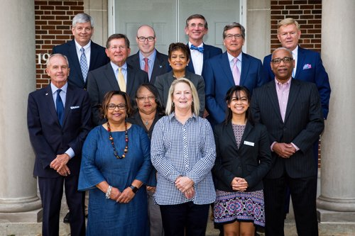 Group photo of 13 Board of Trustees members standing on front steps of the Vernon White Building.