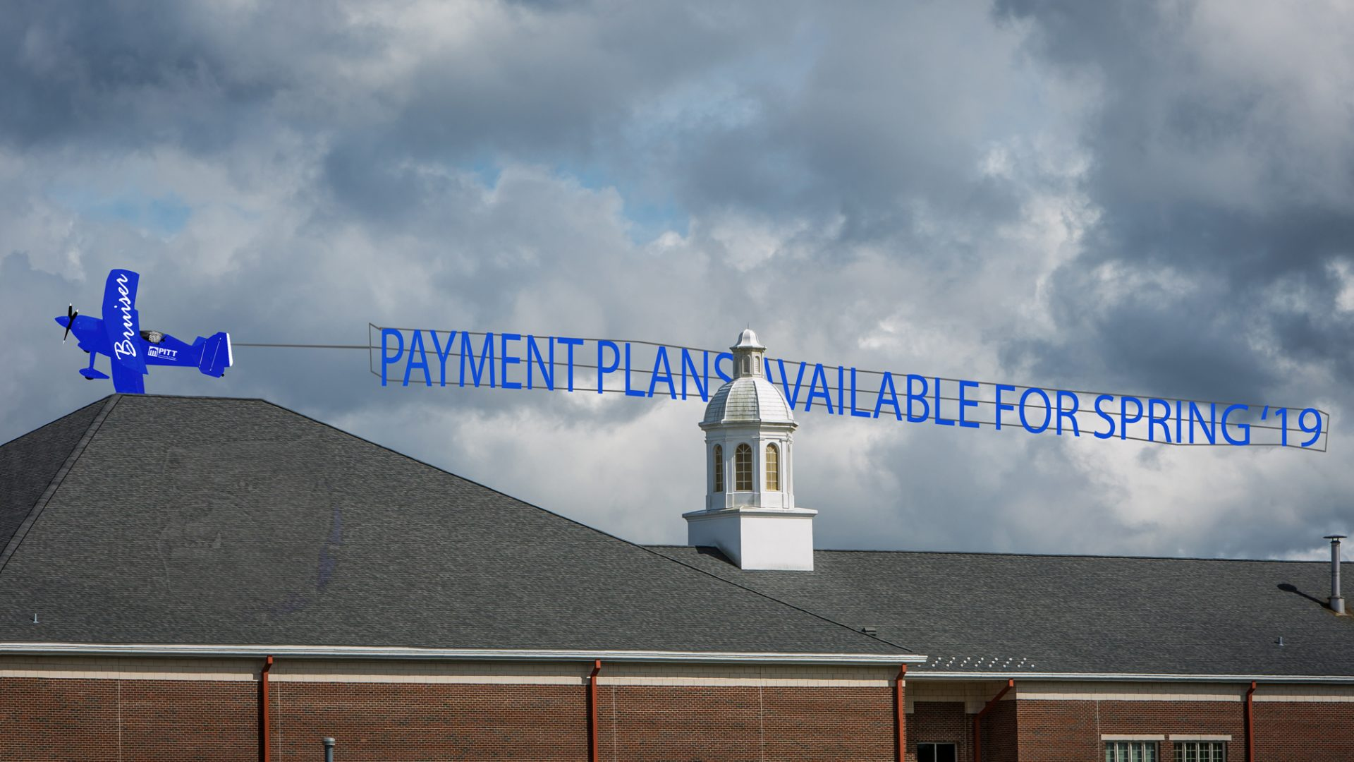 Graphic of blue airplane flying banner announcing payment plans with the Ed & Joan Warren Building in the foreground.