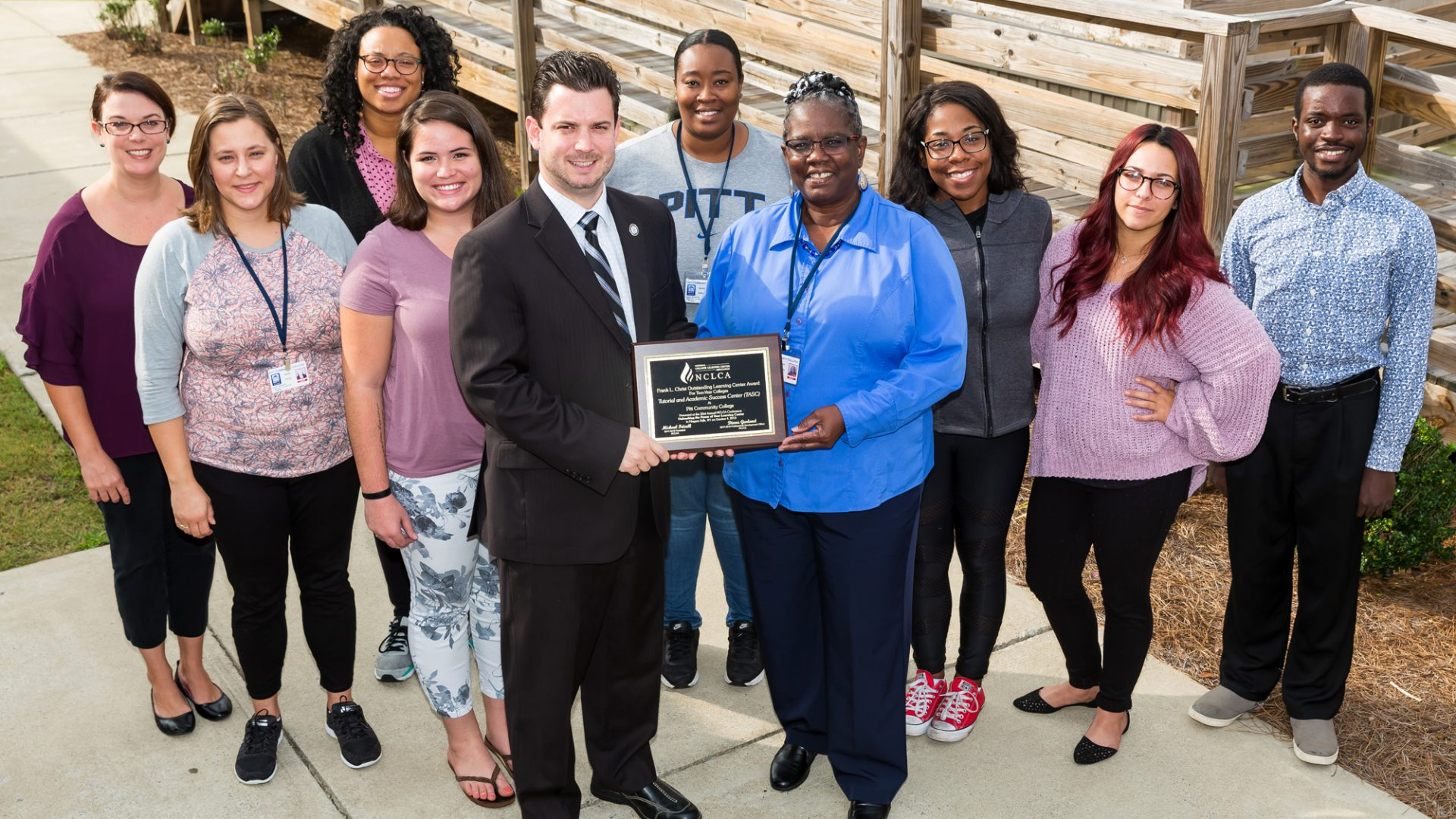 Joined by PCC tutors, TASC Director Nicholas Vick (fifth from left) displays the 2018 Frank L. Christ Outstanding Learning Center of the Year Award for Two-Year Colleges. Pictured with Vick are, left to right: Julianna Juchniewicz, Alicia Young, Alisha Animashaun, Marissa Hunt, Deanna Edwards, Bonnie Sutton, Temptaous McKoy, Sarah Lee and George Cherry.