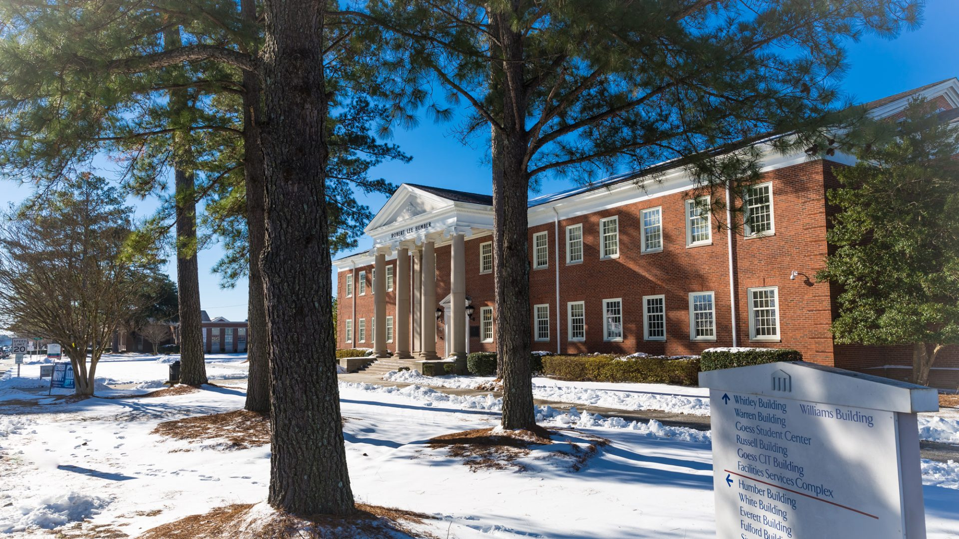 Snow covers the ground in front of the Robert Lee Humber Building on a sunny, clear winter day.