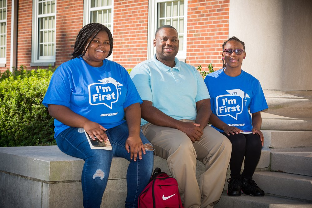 """PCC Director of TRiO Programs Travis Kinsey (center) says the """"IamFirstGen Campaign"""" is a celebration of first-generation college students, like Antwanique Ham (left) and Tonaria Powell. The students, clad in their """"I'm First"""" t-shirts promoting the campaign, are the first members of their respective families to go to college. Both Greenville residents, Ham and Powell have been taking college courses at PCC for the past several years through their enrollment in the Pitt County Schools Early College High School. Now ECHS seniors, Ham is well on her way toward a four-year business degree, while Powell is making steady progress on an Associate in Science Degree from PCC's University Transfer program."""