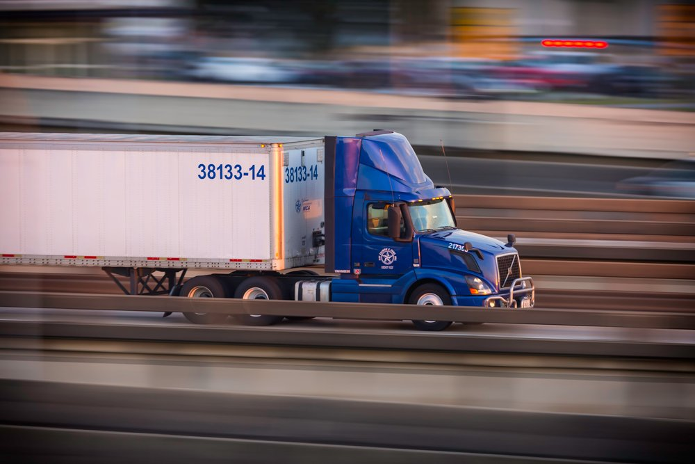 Tractor trailer with blue cab driving on highway.