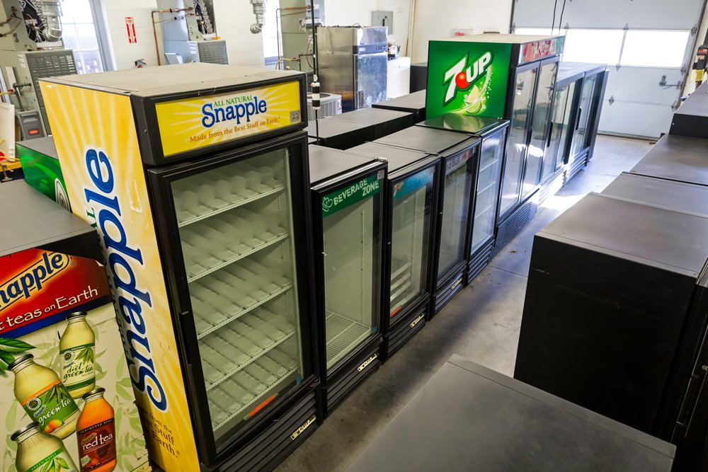 Glass door merchandisers donated by a local beverage distributor lined up in a row in the college's HVAC classroom.