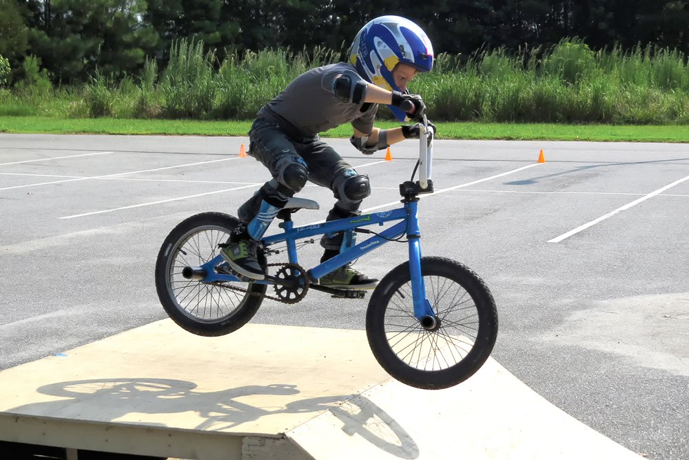 Photo of child on BMX bike jumping a ramp.