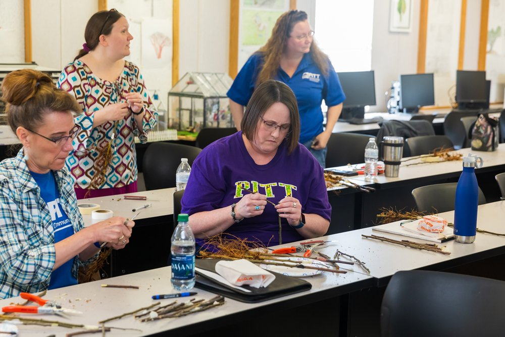 PCC employees try their hand at fruit tree grafting during a professional development seminar.