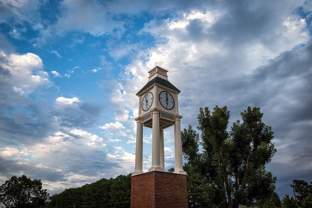 PCC clock tower with cloudy skies behind it.
