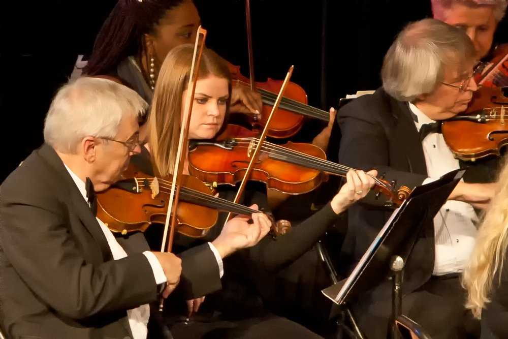 Photo of multiple orchestra members playing violins during a performance.
