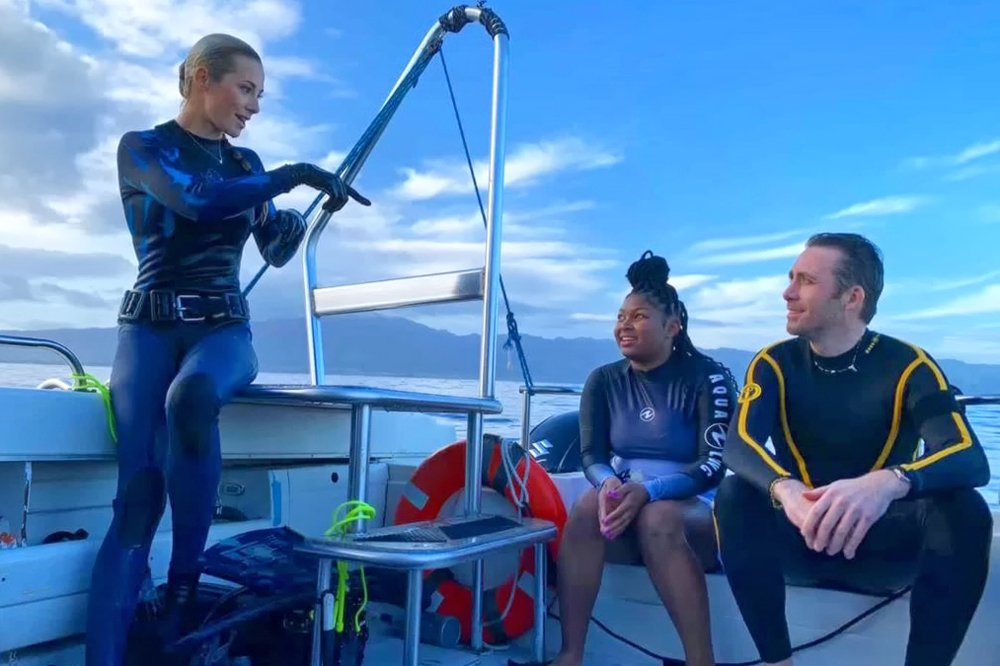 PCC student Ivanya Johnson (center) and Xploration Awesome Planet host Philippe Cousteau Jr. listen to Ocean Ramsey, a shark conservationist and owner of OneOcean Diving, explain the shark behavior they just witnessed while free diving off the Hawaiian coast.