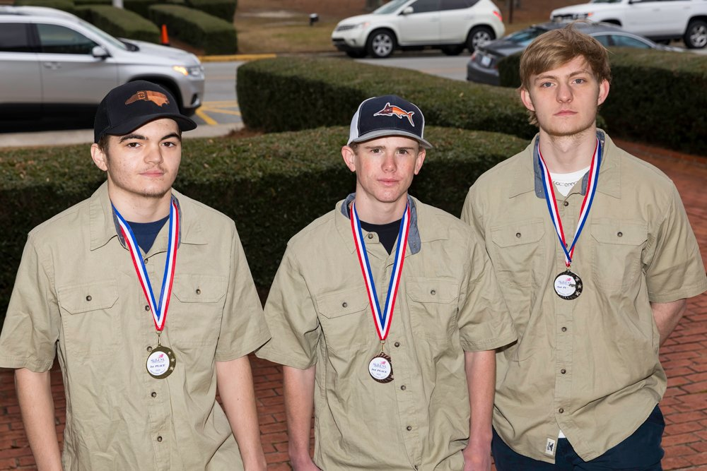 Pitt Community College-Pitt County Schools Technical Academy participants Zachary Huggins, Blake Ross and Mason Jackson, left to right, display medallions they received for their successful performance during the recent SkillsUSA North Carolina​ East Regional Rally in Goldsboro.