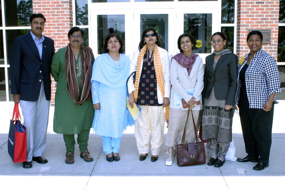 Six members of a group visiting the PCC campus from India pause for a group photo with PCC's Stephanie Rook outside of the Warren Building.