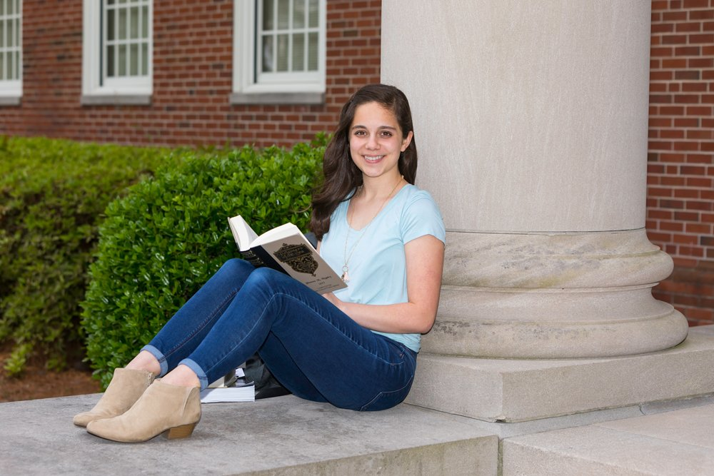 Caroline Puerto smiling at camera while propped against a building column and reading a book.