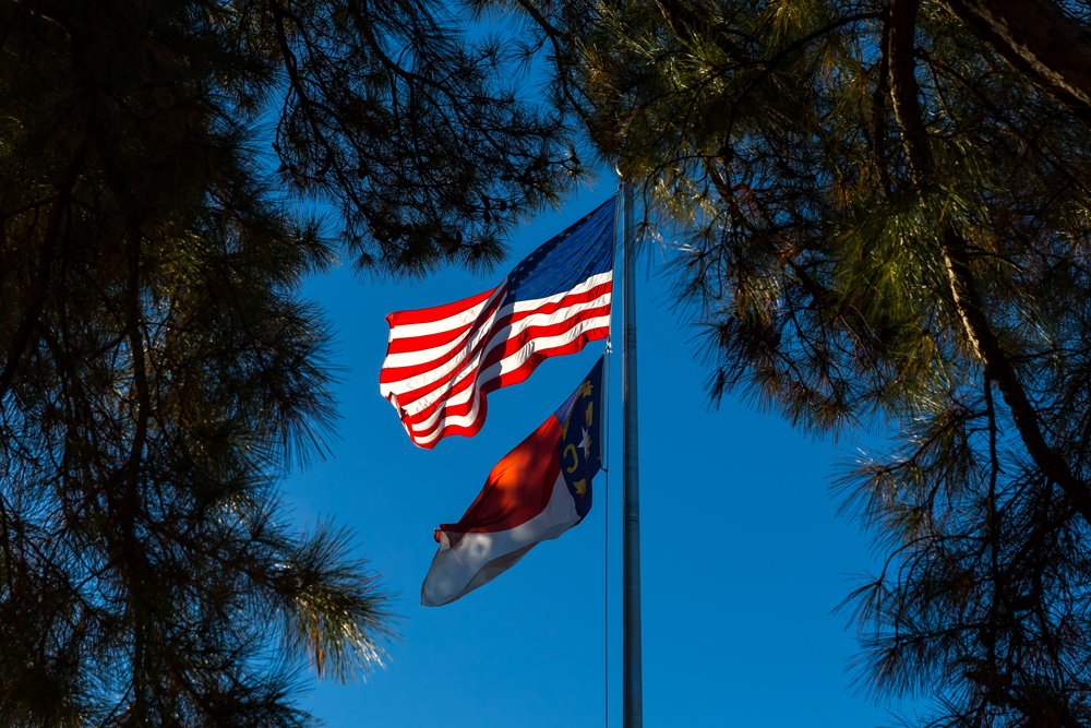 USA and North Carolina flags flying in the breeze against a blue sky and framed by pine trees.