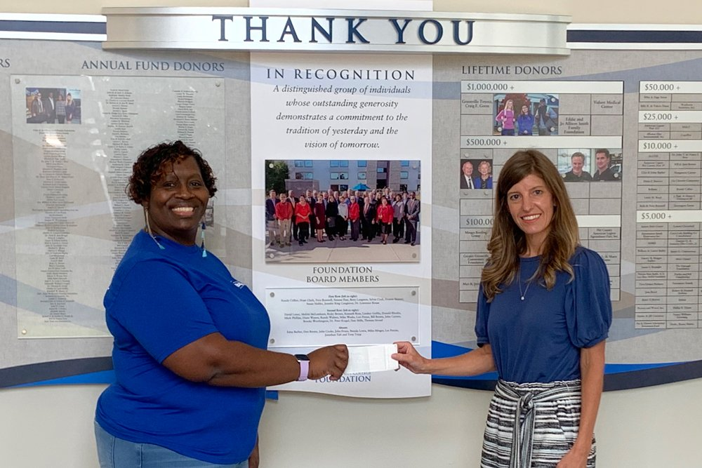 Latina Shelley (left), chair of the State Employees Association of North Carolina's (SEANC) 64th District, presents a $250-check on behalf of her organization to PCC Lead Counselor Olivia Sutton. The donation comes as part of an SEANC community service project and will be used to help stock Pitt's on-campus food pantry, which counseling staff utilize to assist students in need.