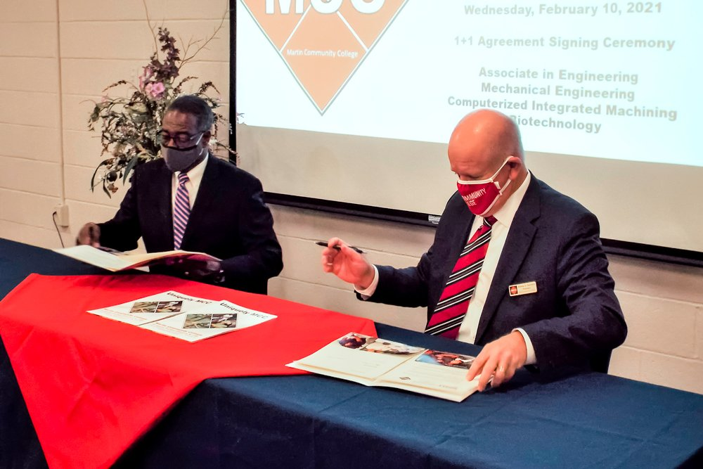During a ceremony at Martin Community College Wednesday morning, Pitt Community College President Lawrence Rouse, left, and MCC President Wesley Beddard sign agreements regarding the transfer of students from Martin into four PCC curricula that lead to jobs in high demand locally.