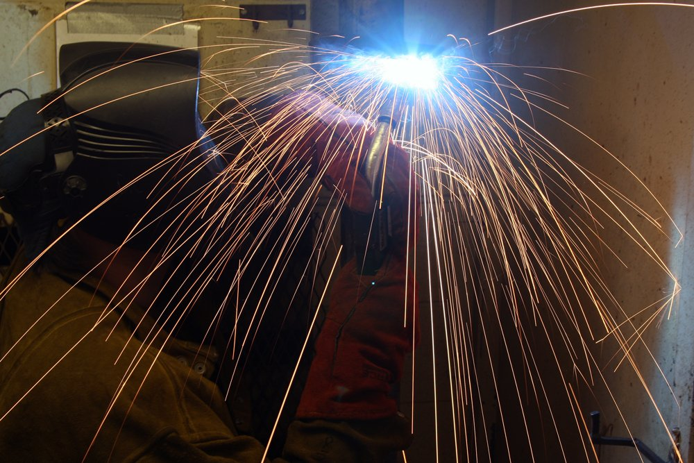 Sparks fly from a welder's torch.