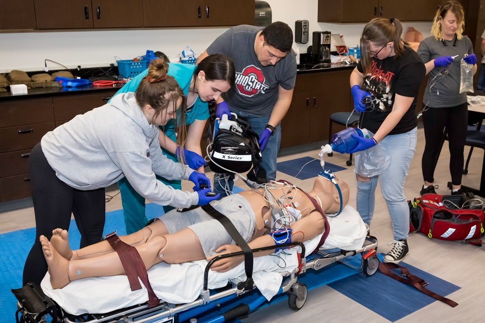 EMS students work to secure a simulated patient to a gurney for transport in an ambulance.